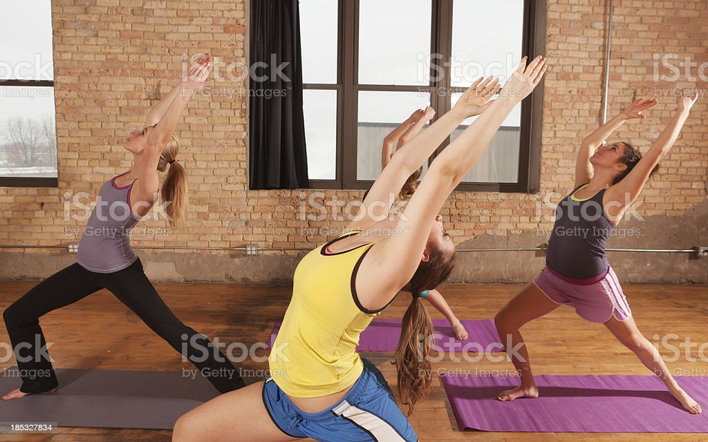 Young Women in High Lunge Pose Attending  Group Yoga Class royalty-free stock photo