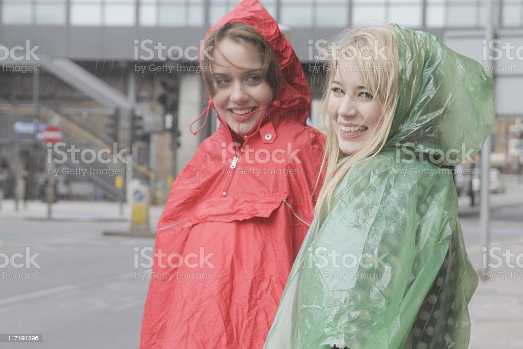 2 young women in raincoats in the city stock photo