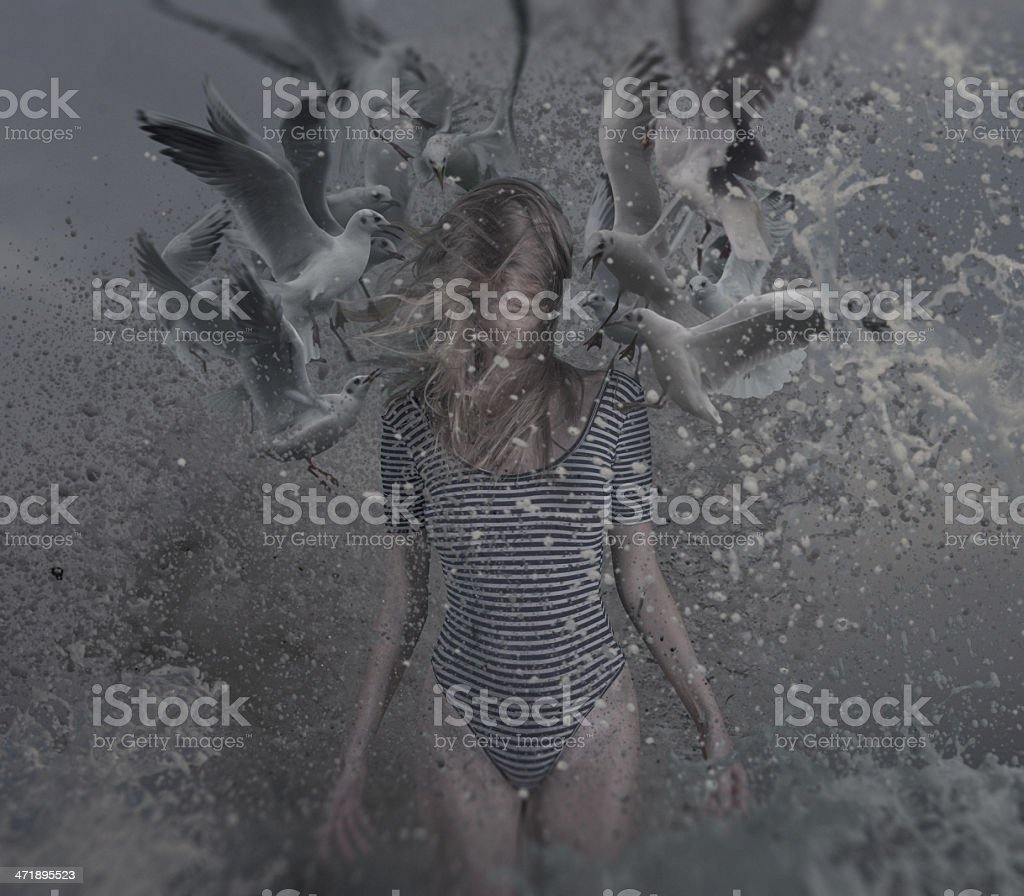 young women in water splashes with sea gulls stock photo