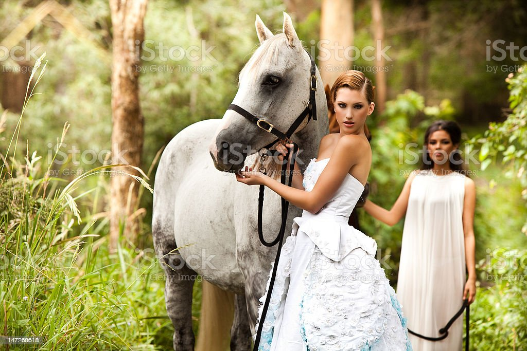 Young Women in White Dresses Outdoors With Horse royalty-free stock photo