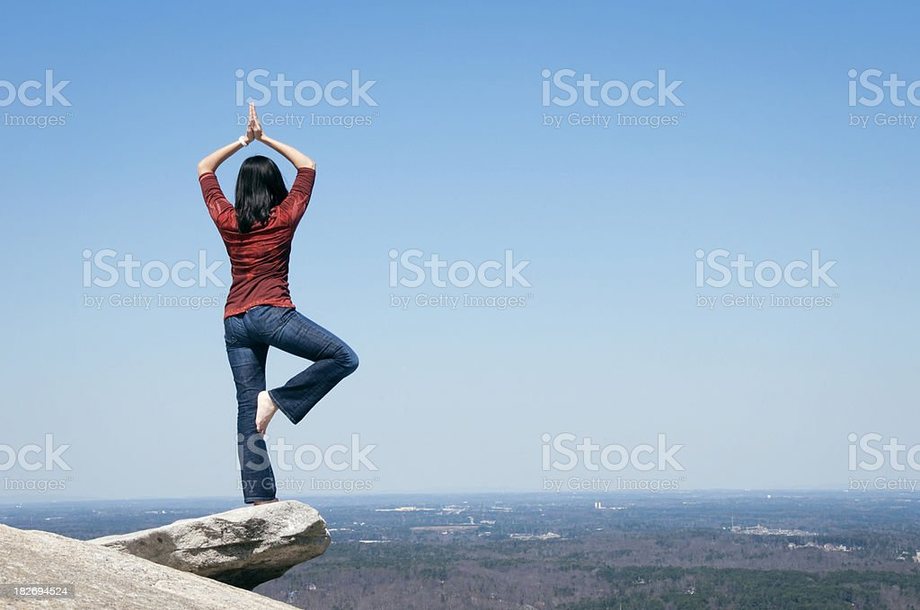 Young Women in yoga tree pose on rock face royalty-free stock photo