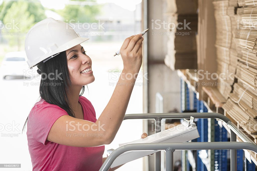 Young women is counting inventory in a warehouse stock photo