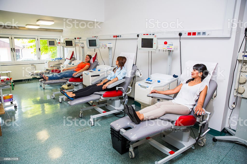 Young women is going to donate blood in  blood bank stock photo