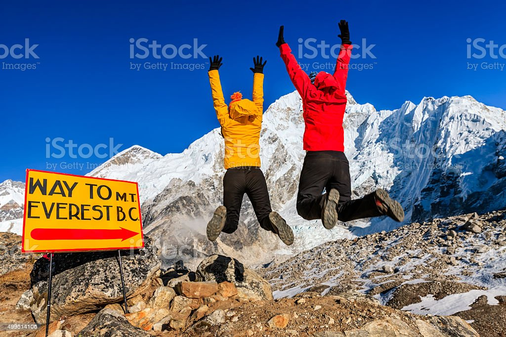 Young women jumping next to signpost 'Way to MountEverest BaseCamp' stock photo
