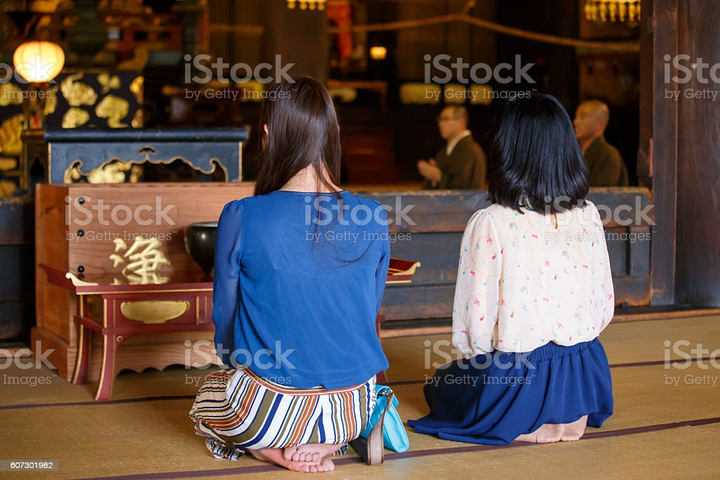 Young women listening to sutra in temple stock photo