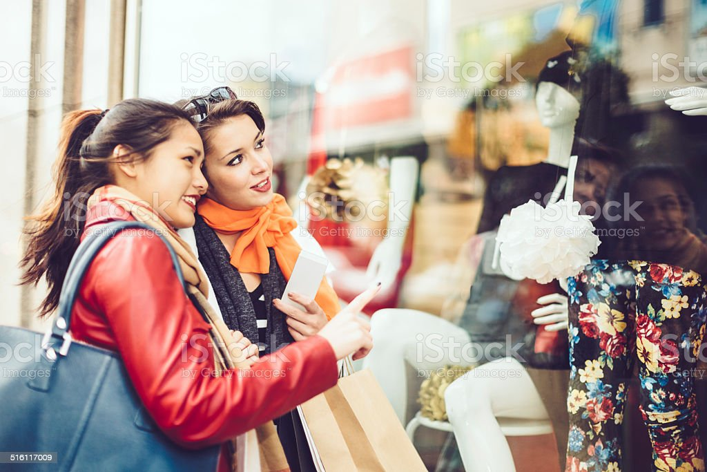 Young women looking at the goods displayed in shop windows stock photo