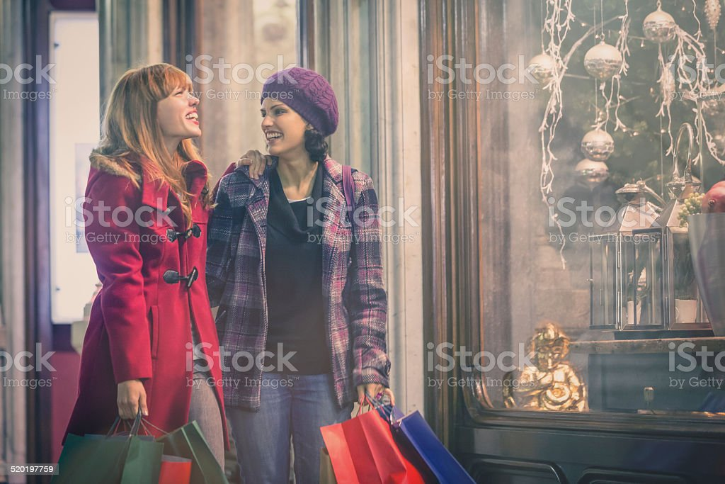 Young women looking for christmas present around old town centre stock photo