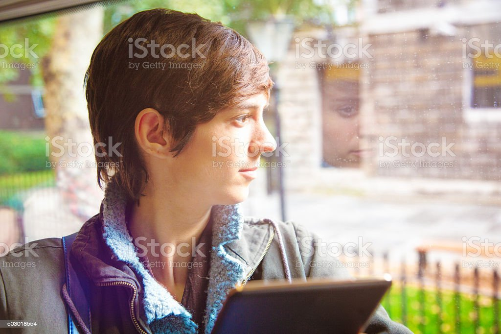 Young women looks pensively through bus window stock photo