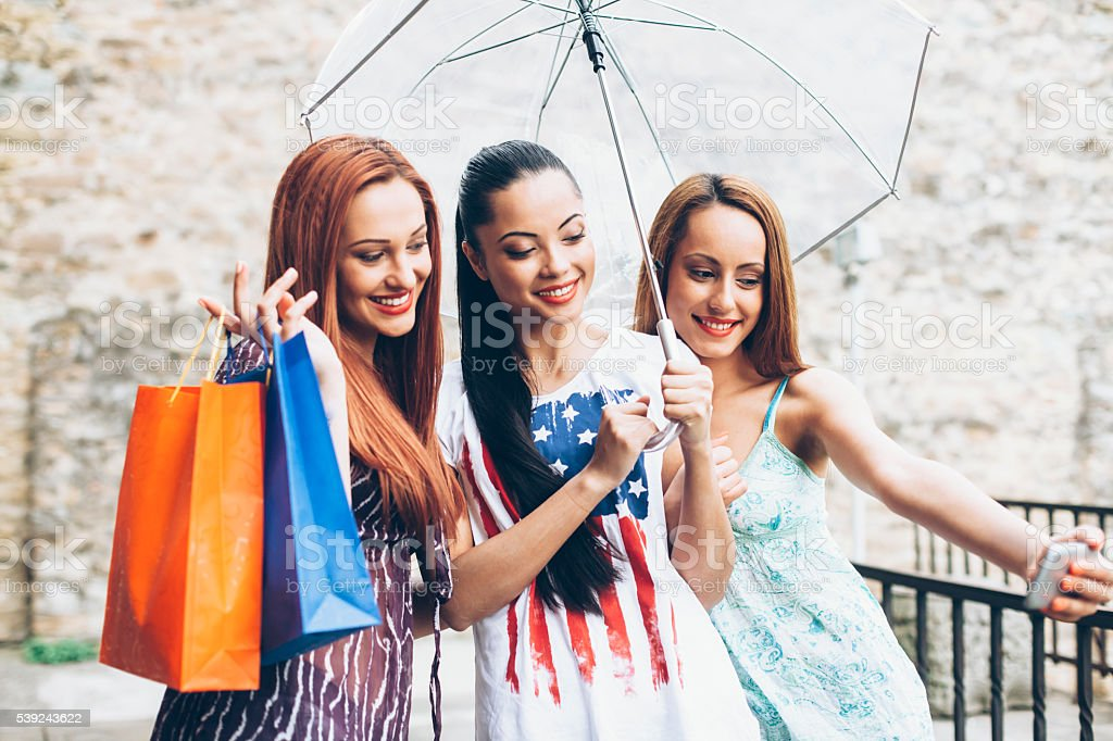 Young women making selfie with umbrella and purchases stock photo