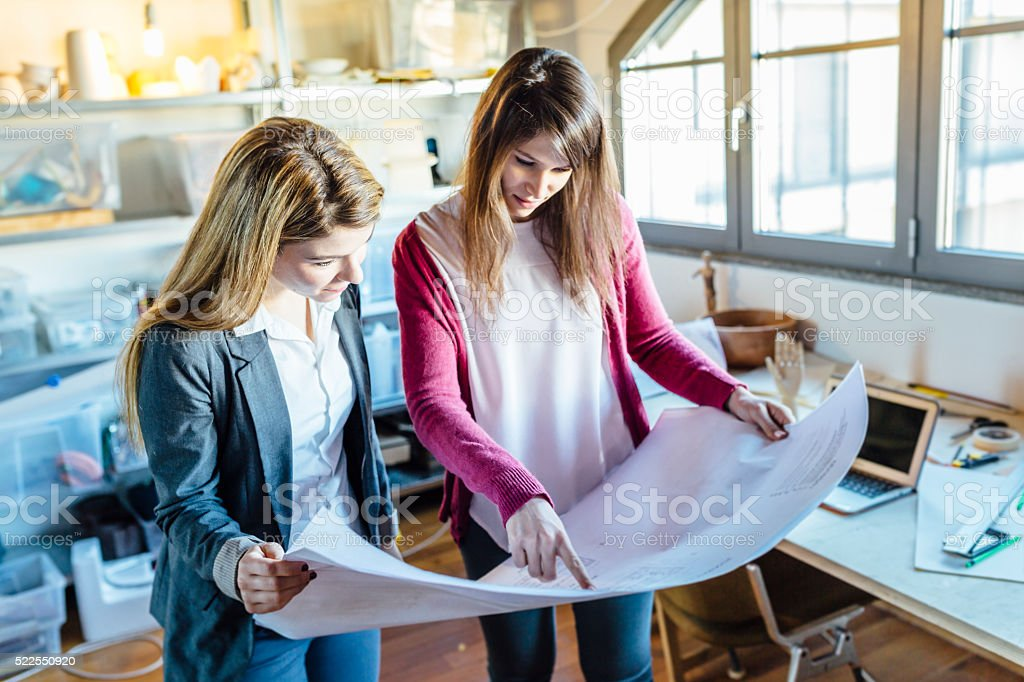 Young women meeting for discussing architect plans stock photo