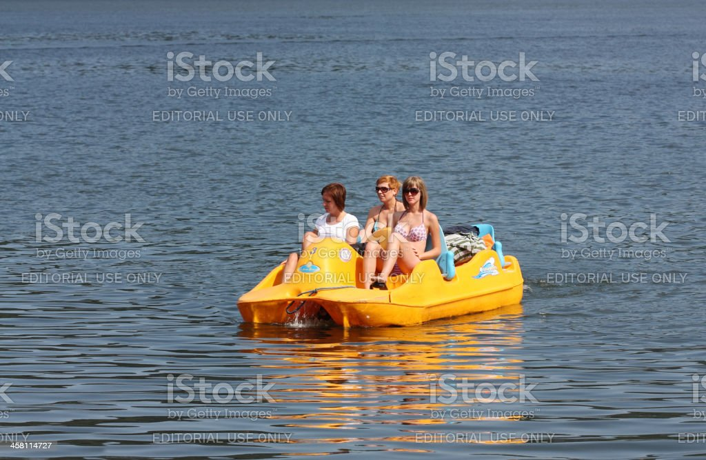 Young women navigate on a paddle boat stock photo