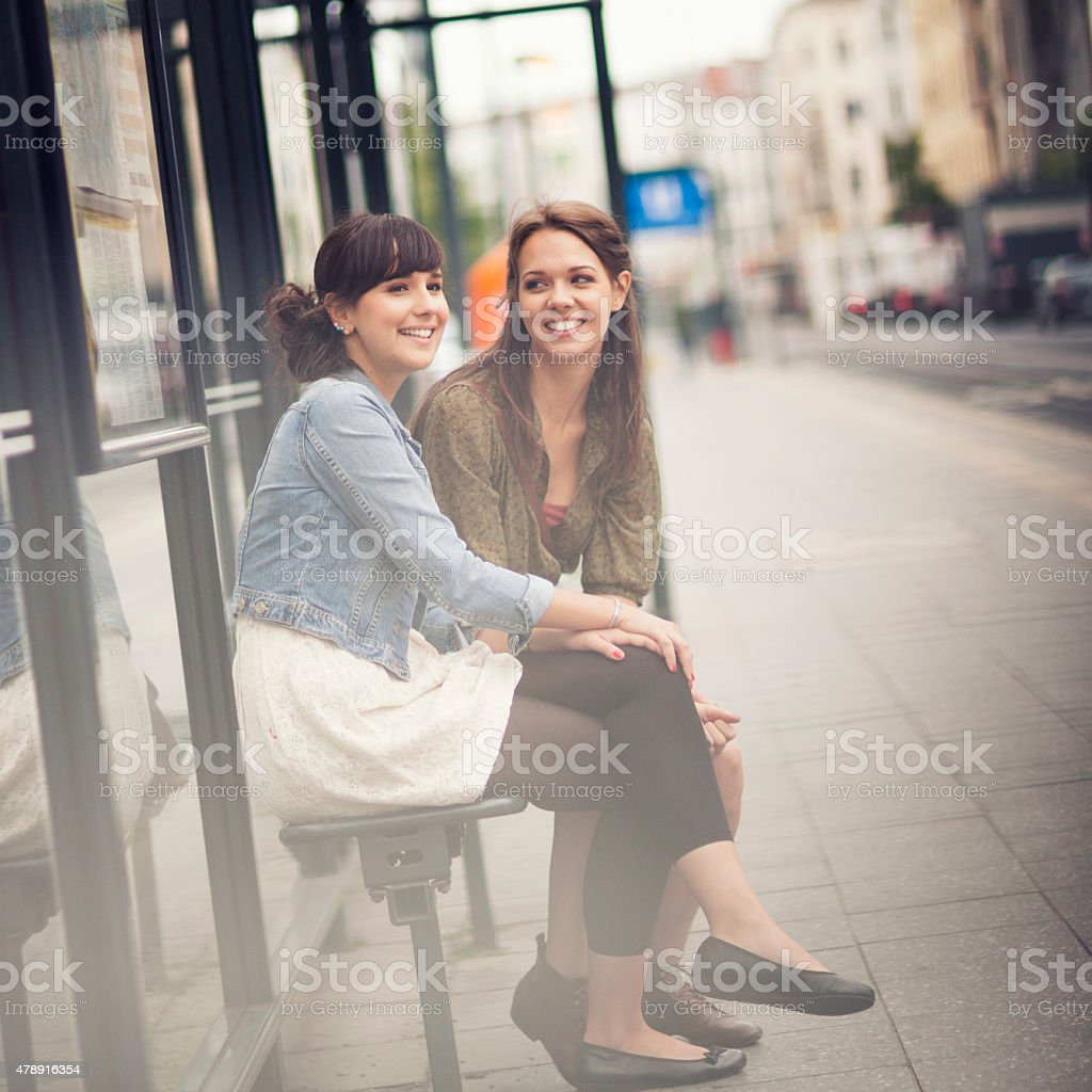 Young women on a bus stop stock photo