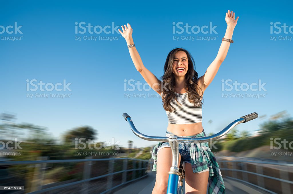 Young Women On Her Beache Cruiser Arms Raised stock photo