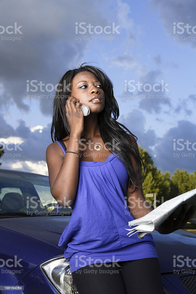 Young women on her cellphone and holding a map royalty-free stock photo