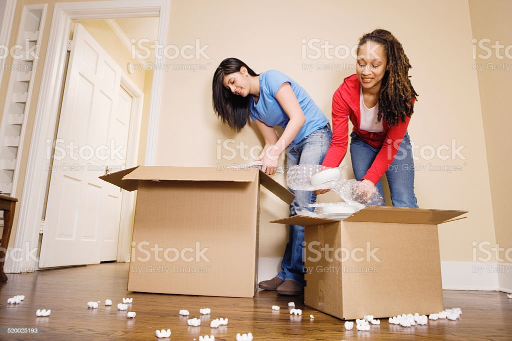 Young women packing boxes, low angle view stock photo