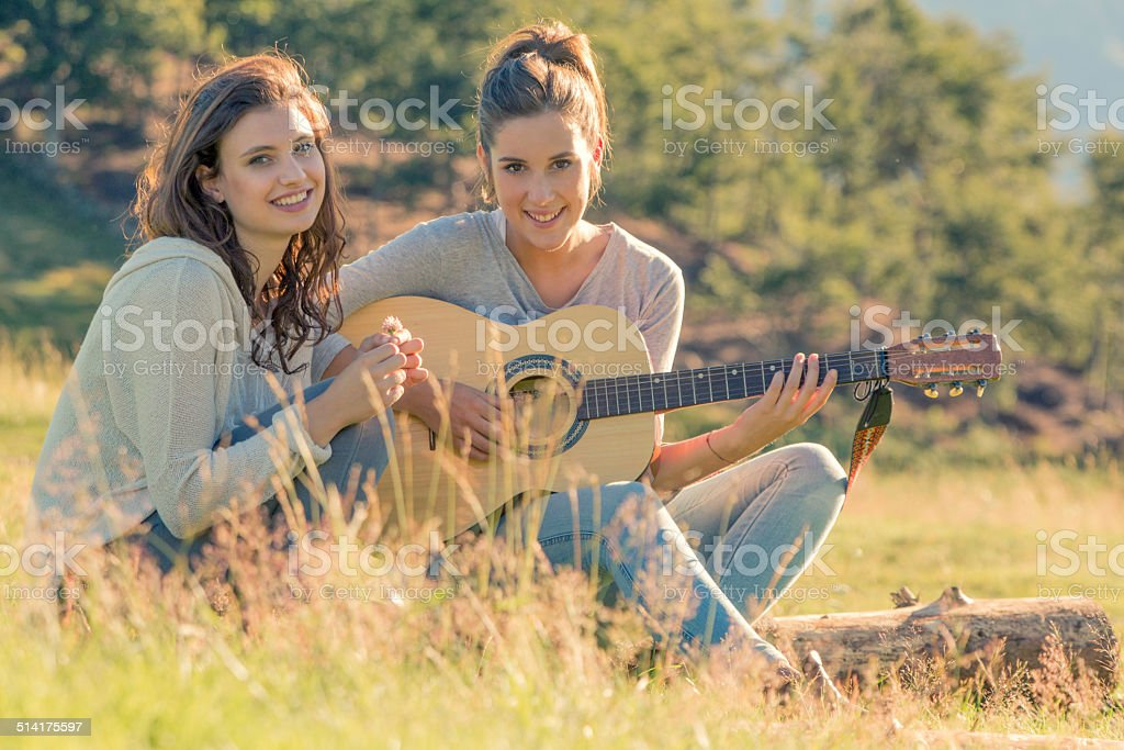 Young women playing guitar looking at camera on sunset outdoor stock photo