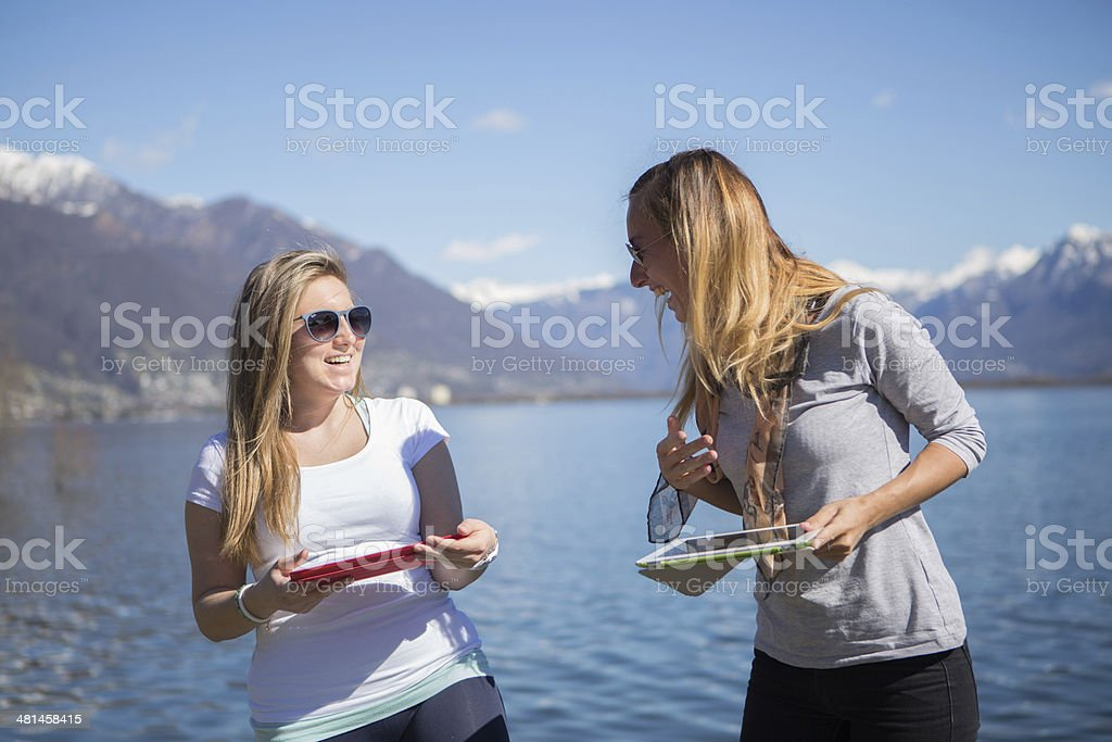 Young women playing with digital tablets royalty-free stock photo