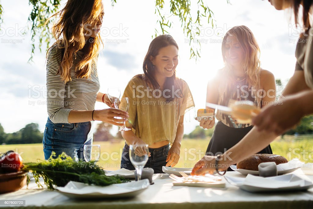 Young women preparing a table for an outdoor dinner party stock photo