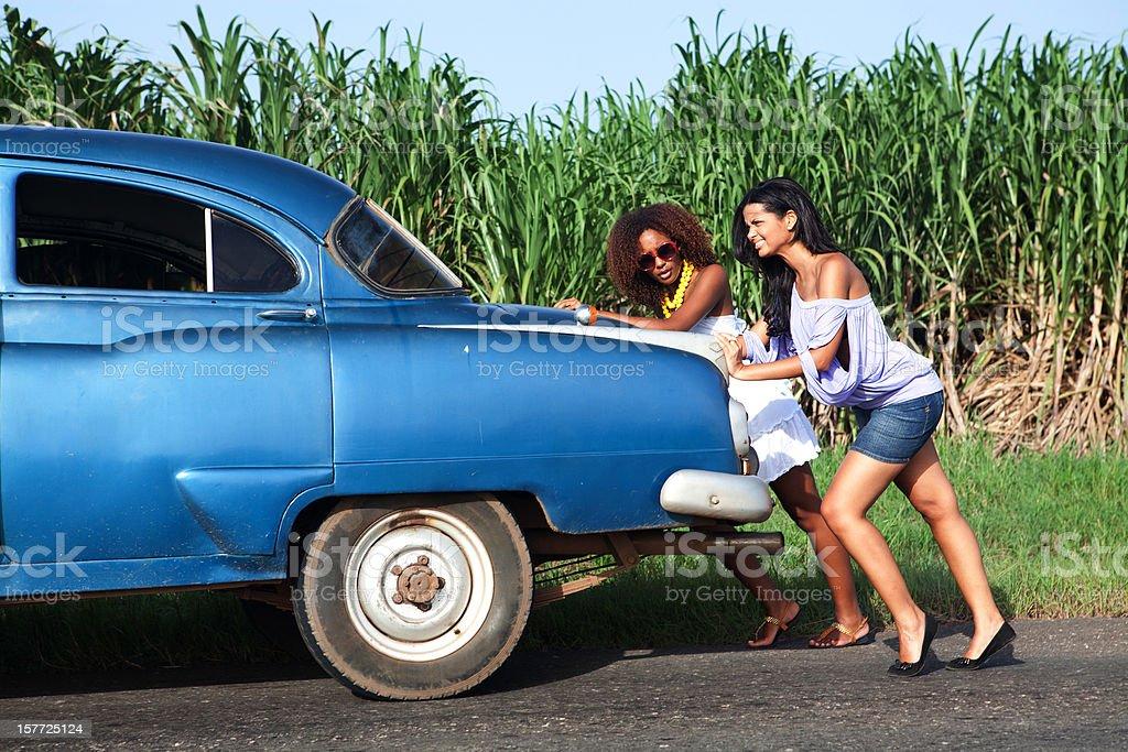 Young women pushing a car stock photo
