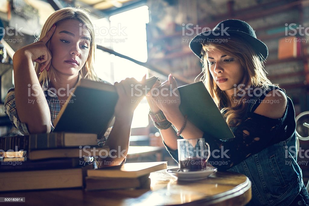 Young women relaxing in a library while studying from books. stock photo