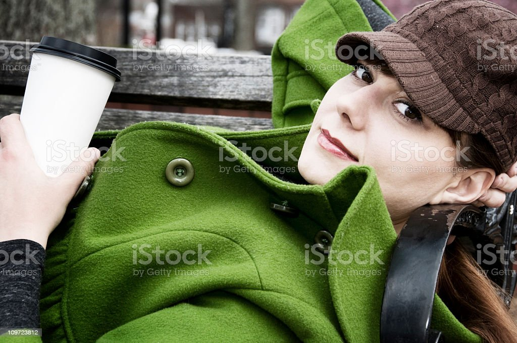 Young Women resting on park bench with coffee stock photo