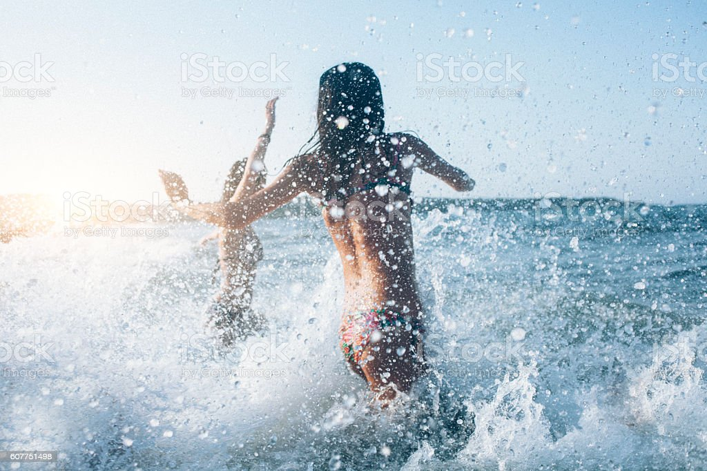 Young women running into the sea stock photo