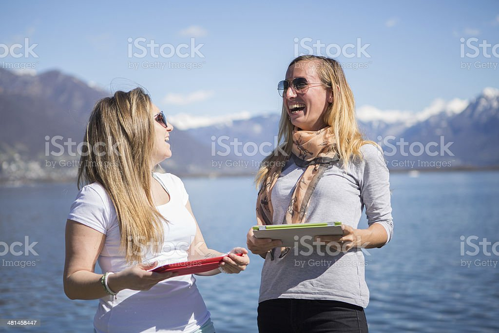 Young women sharing from tablet royalty-free stock photo