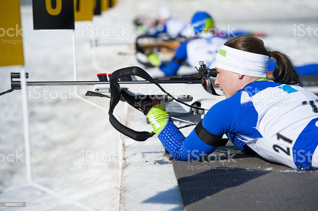 Young women shooting during biathlon competition stock photo