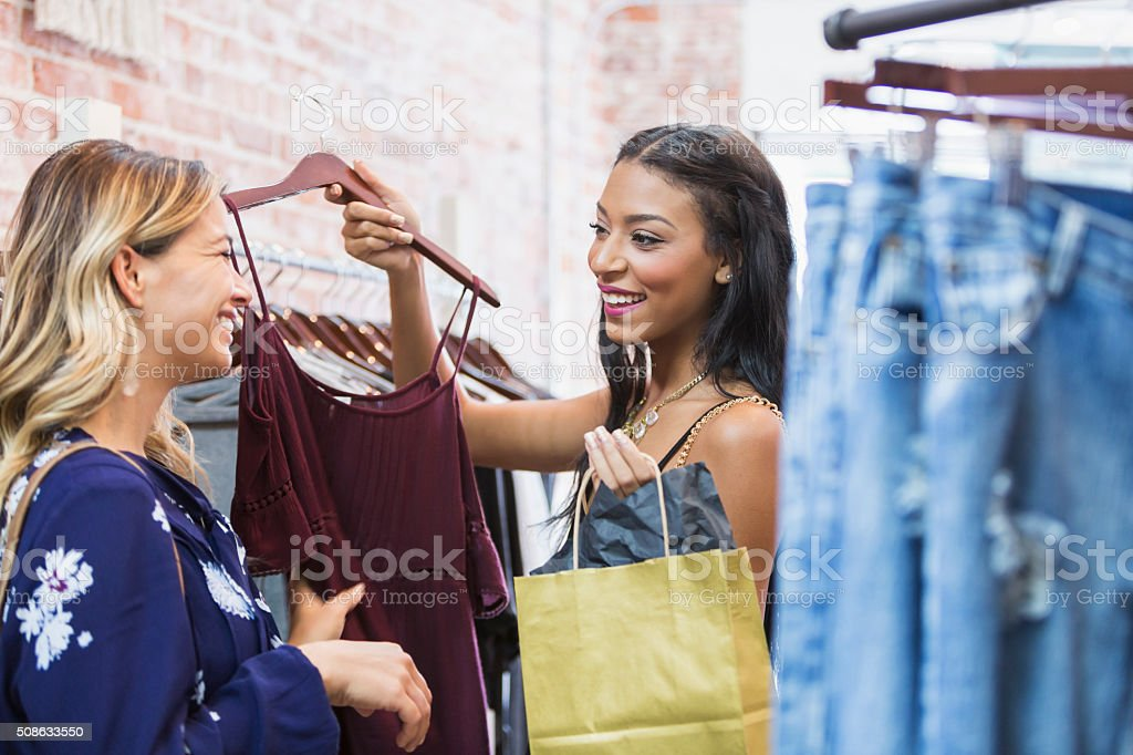 Young women shopping in clothing store stock photo