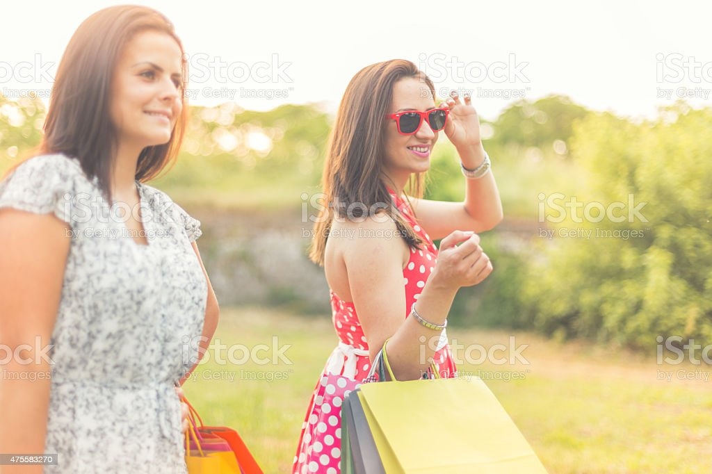 Young women shopping together, walking outdoors stock photo