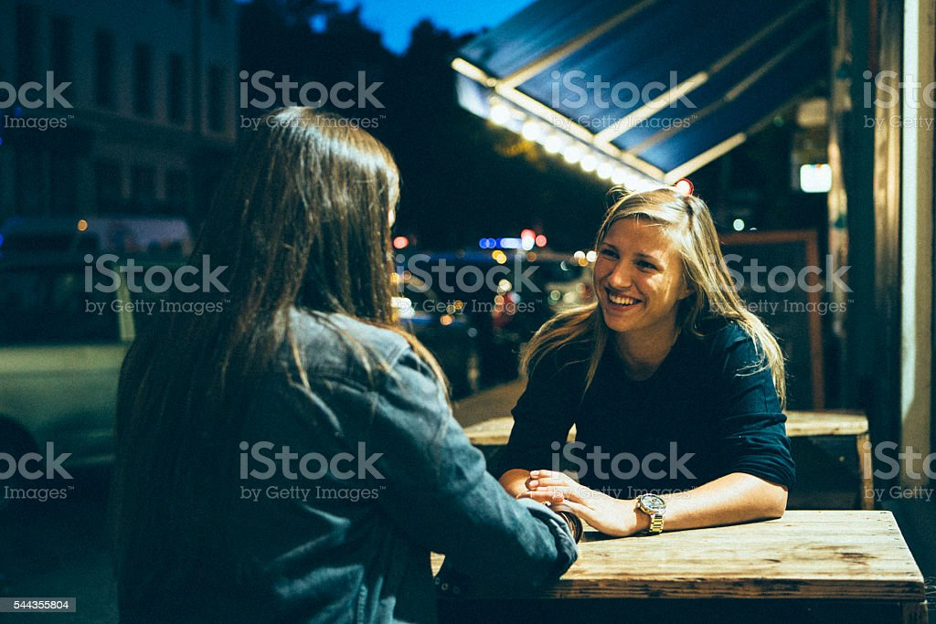 young women sit in sidewalk cafe and talk, Berlin stock photo