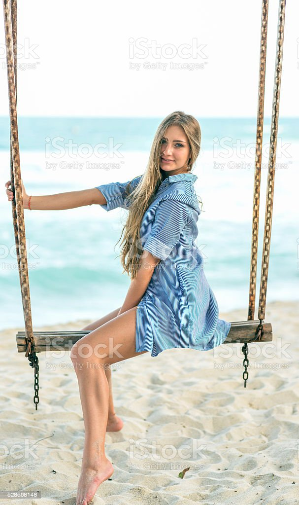 Young women sittiing on the swing stock photo