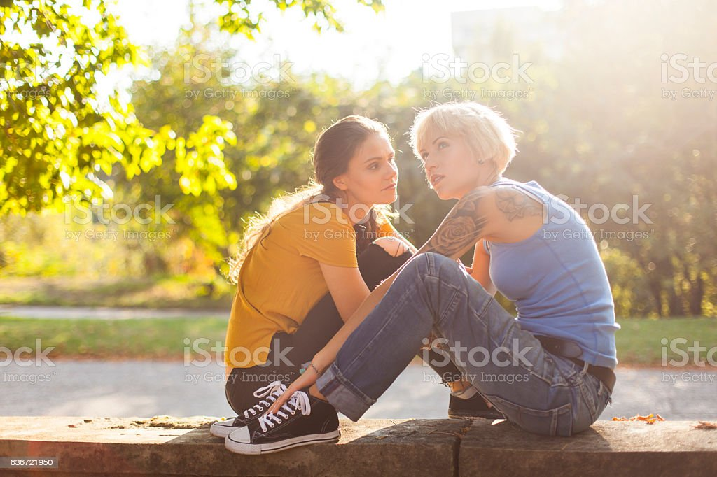 Young women sitting face to face in park stock photo