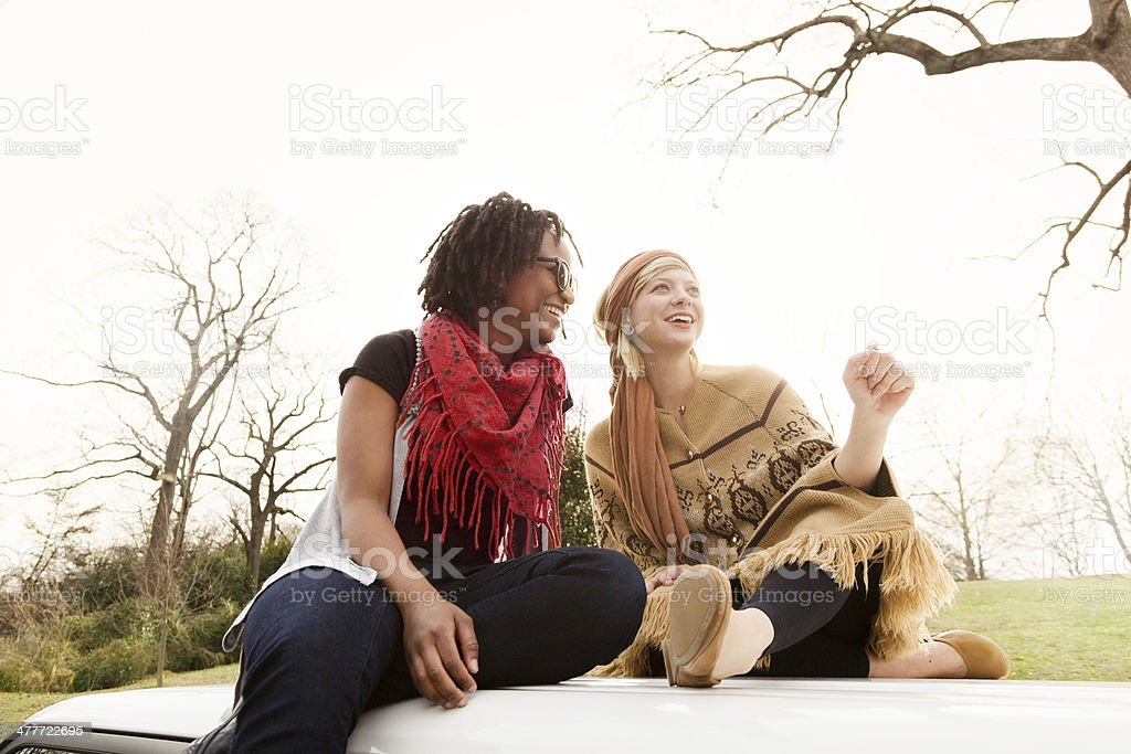 Young Women Sitting on a Car royalty-free stock photo