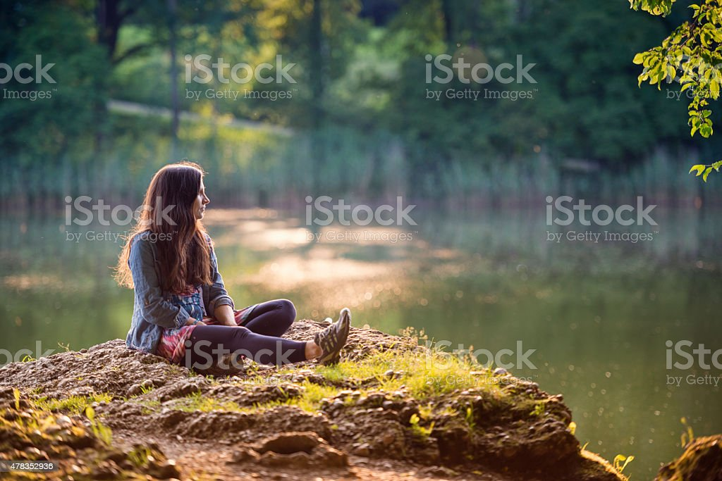 young women sitting on a lake stock photo