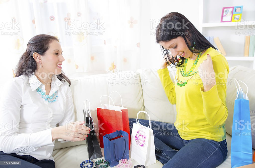 Young women sitting on couch with shopping bags and jewelry royalty-free stock photo