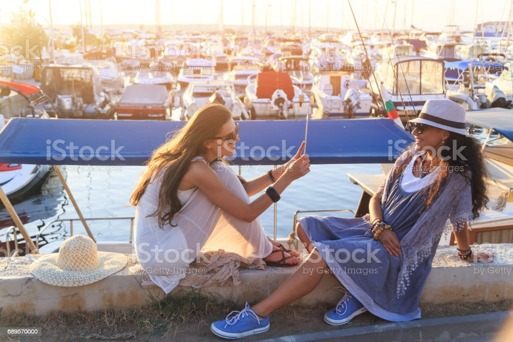 Young women sitting on harbor and taking selfie stock photo
