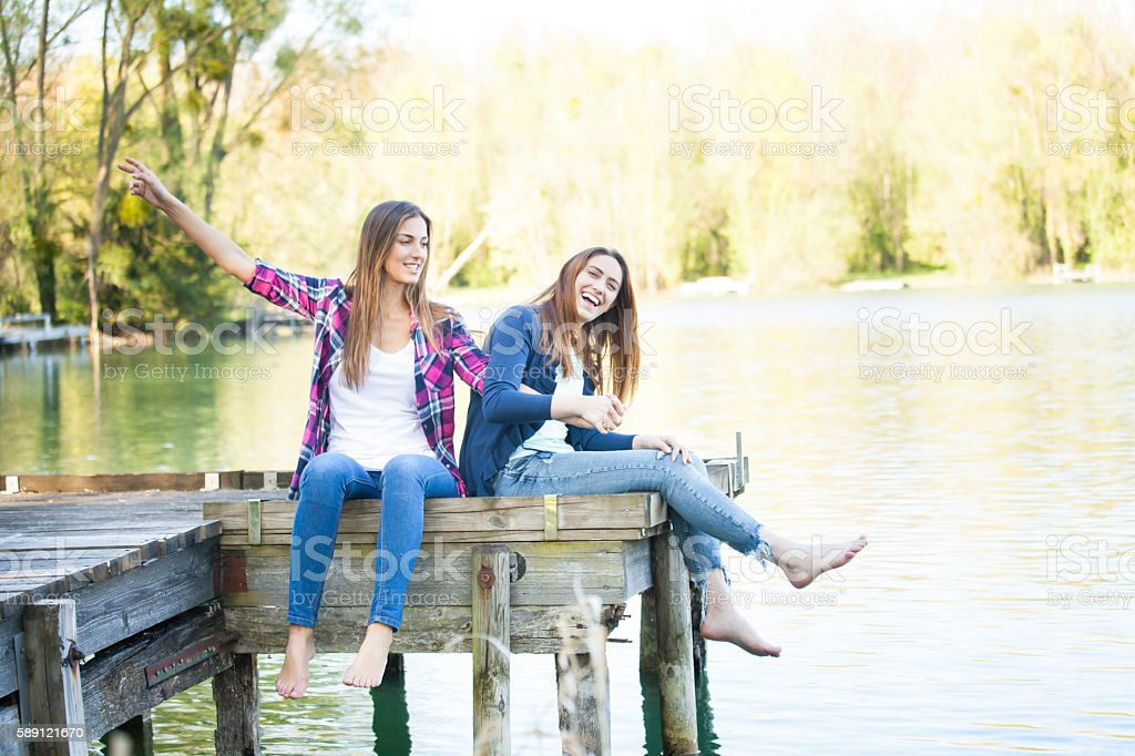 Young women sitting on jetty and having fun stock photo