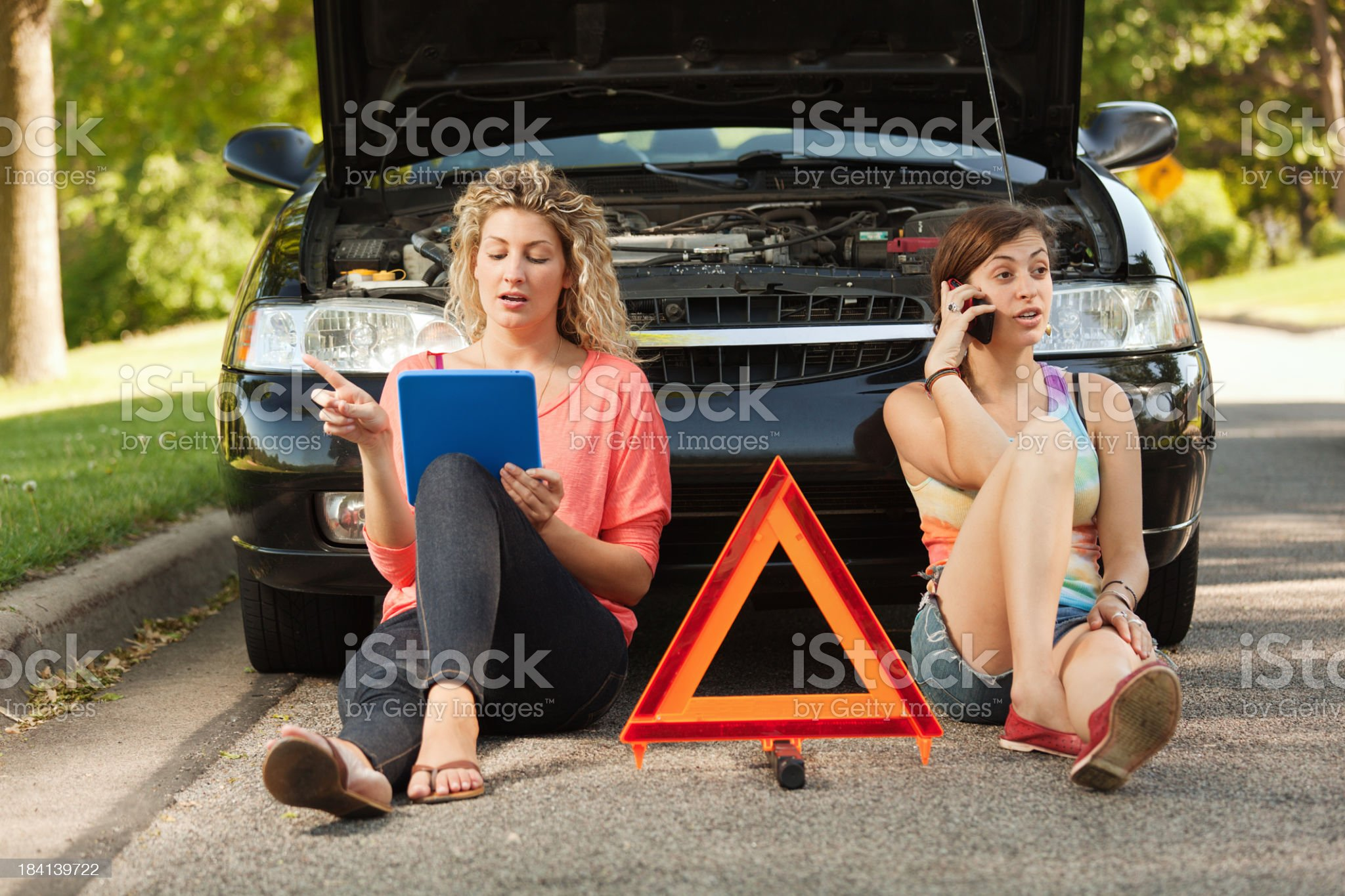 Young Women Solving Car Breakdown with Mobile Phone, Tablet Computer royalty-free stock photo