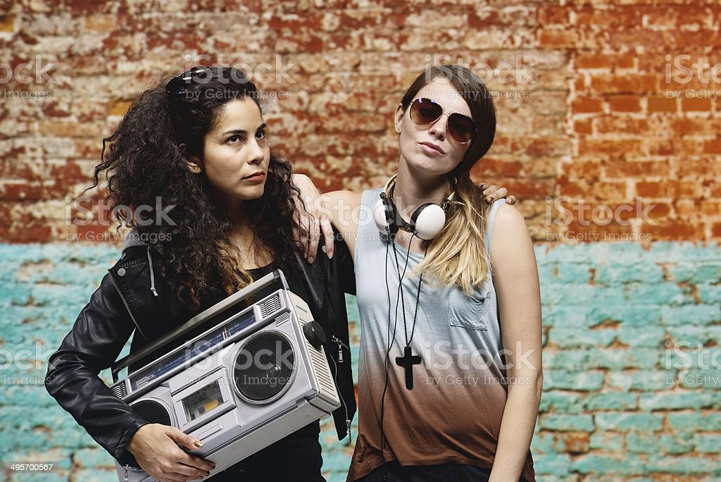 Young women standing in front of brick wall royalty-free stock photo