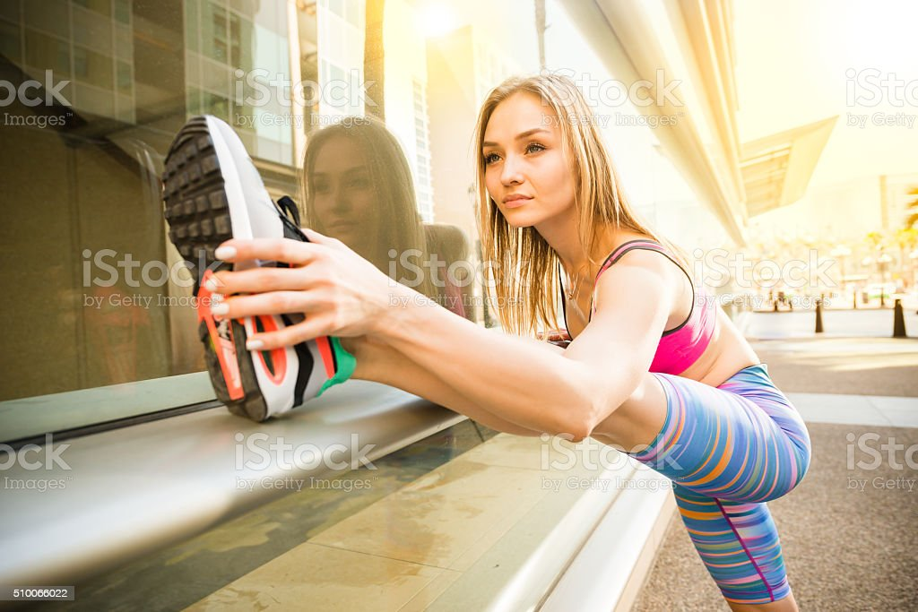 Young Women Stretching With Building Windows Refections Behind stock photo