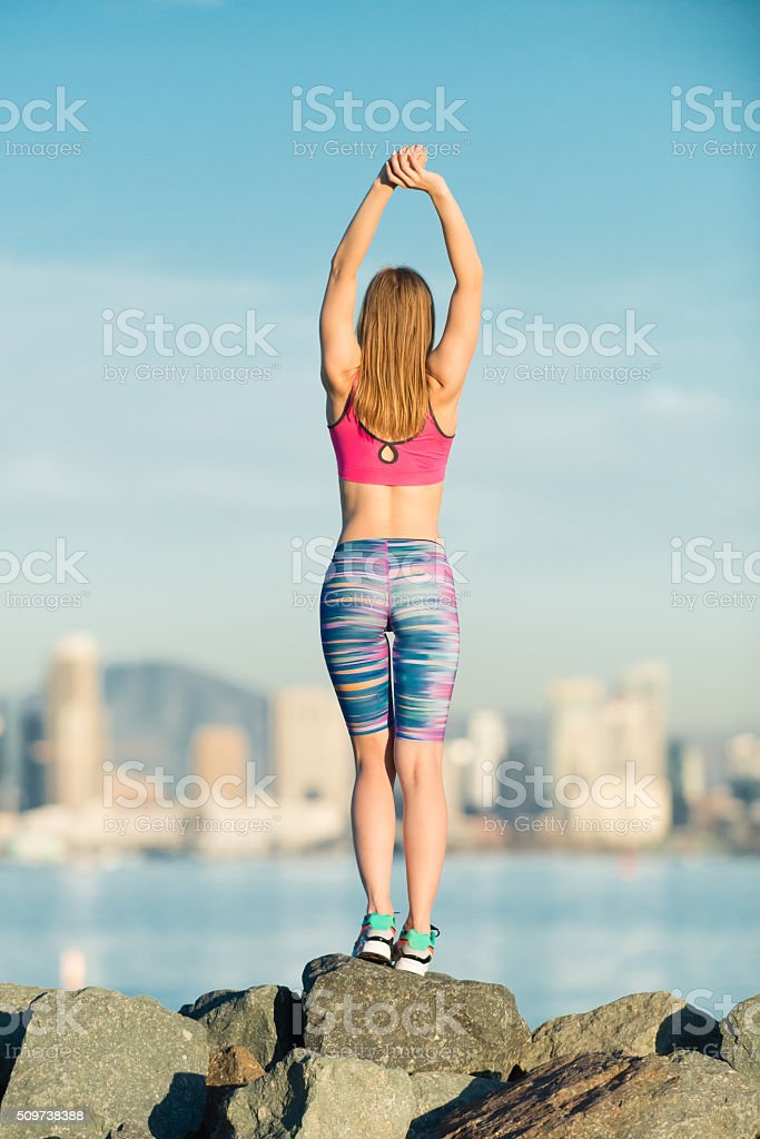 Young Women Stretching With San Diego City Skyline Behind stock photo