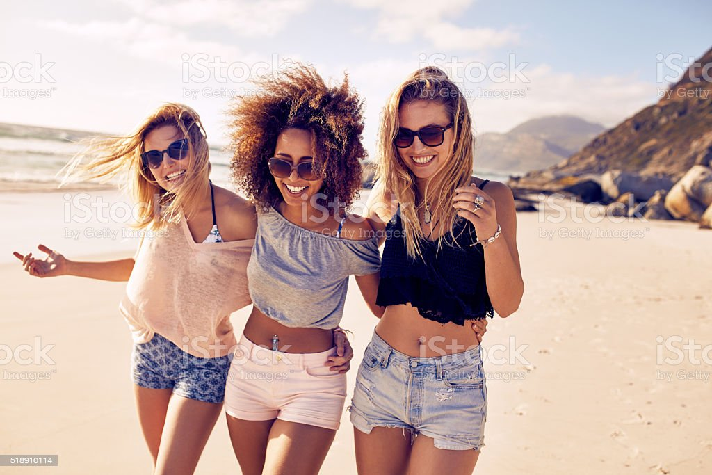Young women strolling along a beach stock photo