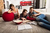 Young women studying at home and using cell phone.