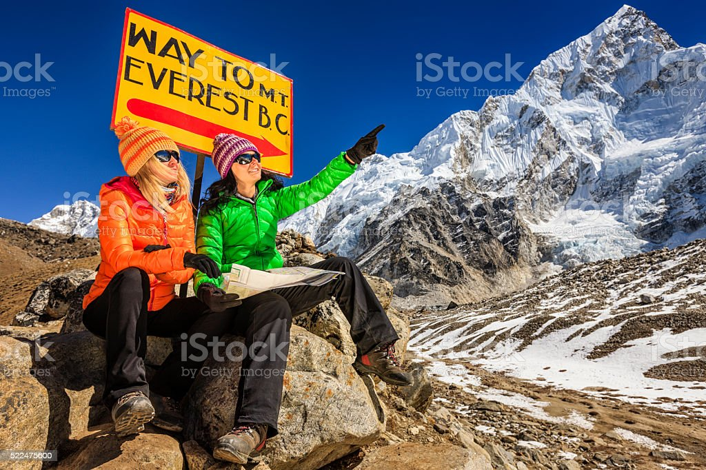 Young women studying map next to signpost, Nepali Himalaya stock photo