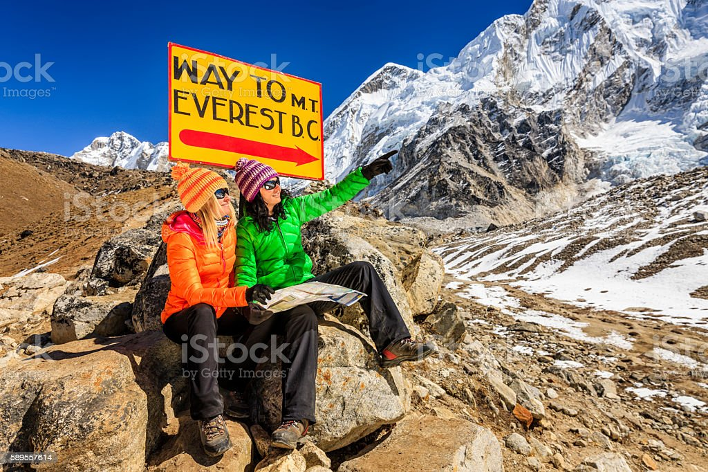 Young women studying map next to signpost, Nepali Himalaya stock photo