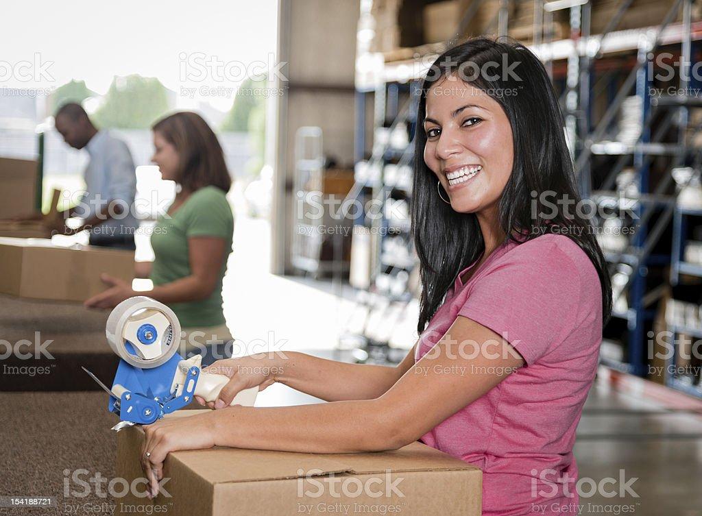 Young women taping a box stock photo