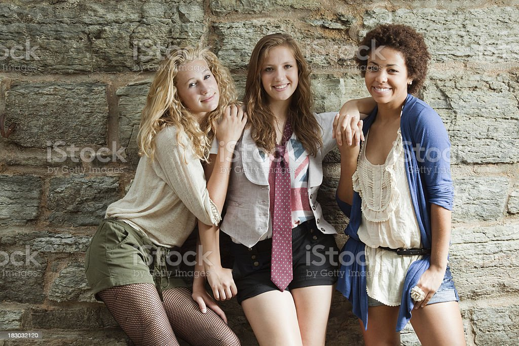 Young Women: Three Happy Smiling Teenage Girls by Stone Wall royalty-free stock photo