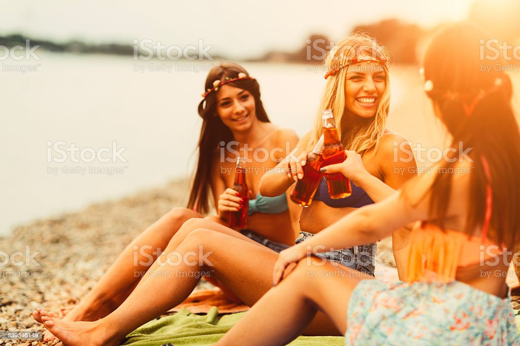 Young Women Toasting With Bottles On The Beach. stock photo