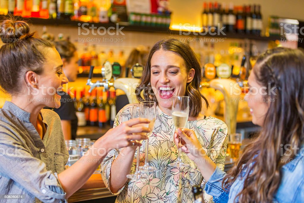 Young Women Toasting With Champagne in a Bar stock photo